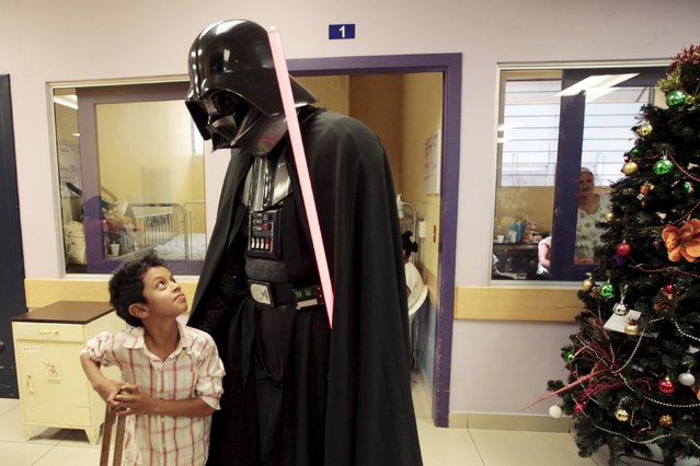 A cosplayer dressed as Darth Vader from the Star Wars movie series interacts with a child during a charity event organised by the El Salvador Star Wars fan club at the Benjamin Bloom National Children's Hospital in San Salvador, El Salvador December 14, 2015. (Photo by Jose Cabezas/Reuters)