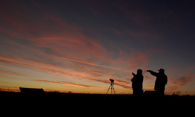 """People are silhouetted against the sky at dusk as they watch the alignment of Saturn and Jupiter, Monday, December 21, 2020, in Edgerton, Kan. The two planets are in their closest observable alignment since 1226. Appearing a tenth of a degree apart, the alignment known as the """"great conjunction"""" has also been called the """"Christmas Star"""". (Photo by Charlie Riedel/AP Photo)"""