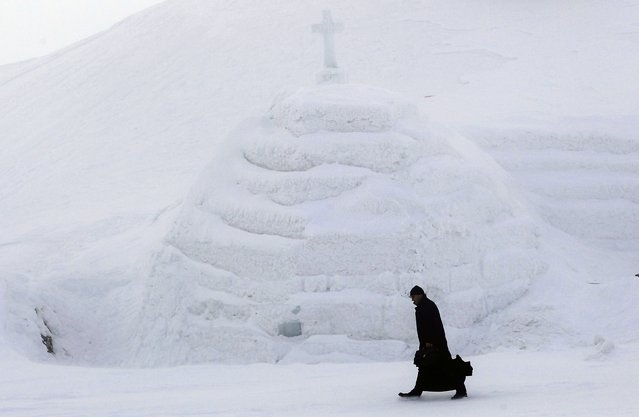 A priest arrives for the inauguration of a church made entirely from ice at Balea Lac resort in the Fagaras mountains January 29, 2015. (Photo by Radu Sigheti/Reuters)