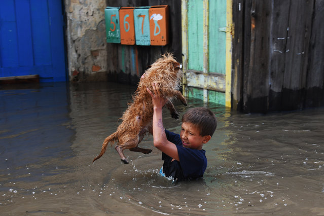 A boy holds his dog above water in the city of Chita hit by floods, the state of emergency declared in the Transbaikal Territory, Russia as the Chita River bursts its banks on July 10, 2018. (Photo by Yevgeny Yepanchintsev/TASS)