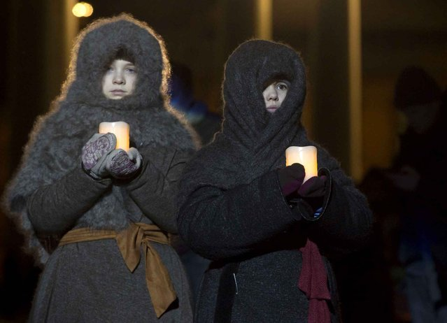 Children dressed as children of Leningrad Siege carry candles in St.Petersburg, Russia, Tuesday, January 27, 2015, during a performance in memory of people who perished during the Nazi German and Finnish Siege of Leningrad, now St.Petersburg, during a public action marking the 71st anniversary of the battle that broke the siege. The Nazi German and Finnish siege and blockade of Leningrad was broken on Jan. 18, 1943 but finally lifted Jan. 27, 1944. (Photo by Dmitry Lovetsky/AP Photo)