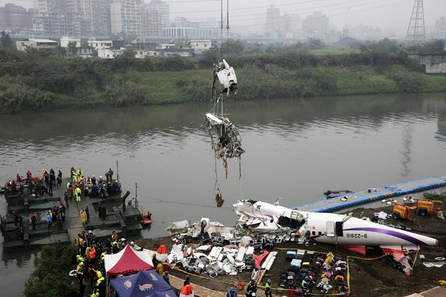 Rescuers lift part of the wreckage of TransAsia Airways plane Flight GE235 after it crash landed into a river, in New Taipei City, February 5, 2015. Taiwanese rescue officials refused to give up hope of finding 12 people still missing on Thursday more than 24 hours after a TransAsia Airways plane crashed into a Taipei river, killing at least 31. (Photo by Reuters/Stringer)