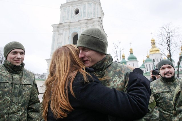 """A woman embraces a member of the newly created Ukrainian interior ministry battalion """"Saint Maria"""" after a ceremony before they head to military training, in front of St. Sophia Cathedral, in Kiev, February 3, 2015. (Photo by Valentyn Ogirenko/Reuters)"""