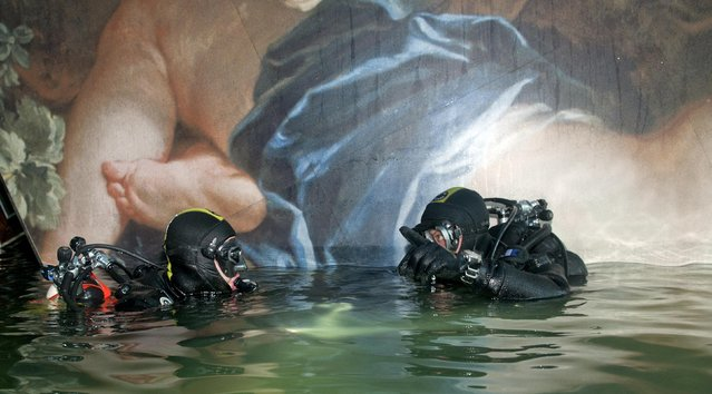 Two scuba divers of Italian Navy inspect inside the Costa Concordia cruise ship which ran aground off the west coast of Italy at Giglio island and lies on its side, half-submerged and threatening to slide into deeper waters in this photo released on in this January 23, 2012 file photo. (Photo by Marina Militare/Reuters)