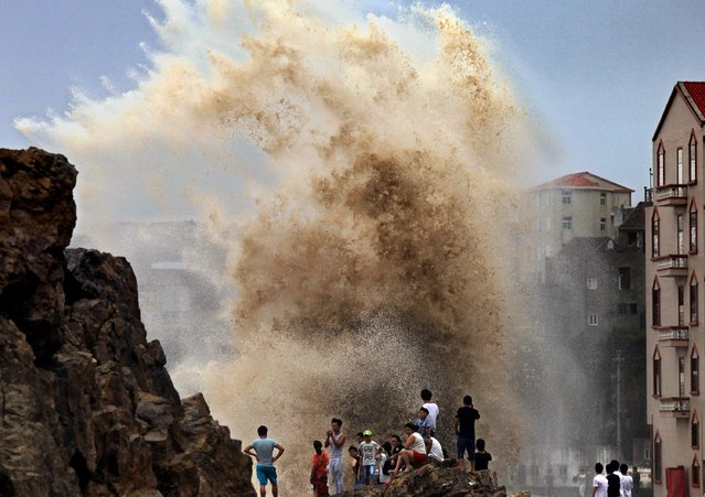Residents gather to see huge waves stirred up by strong wind as typhoon Soudelor draws near the mainland of China in Wenling, east China's Zhejiang province  on August 8, 2015. Typhoon Soudelor battered Taiwan with fierce winds and rain, leaving four people dead and a trail of debris in its wake as it takes aim at mainland China. (Photo by AFP Photo/Stringer)