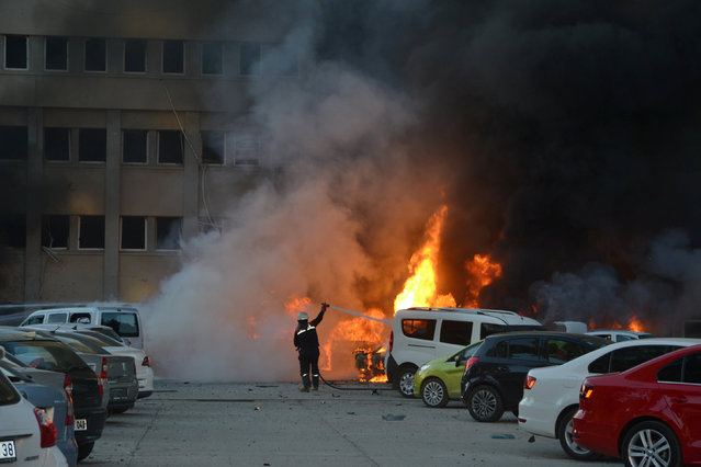 A firefighter tries to extinguish burning vehicles after an explosion outside the governor's office in the southern city of Adana, Turkey, November 24, 2016. (Photo by Ihlas News Agency/Reuters)
