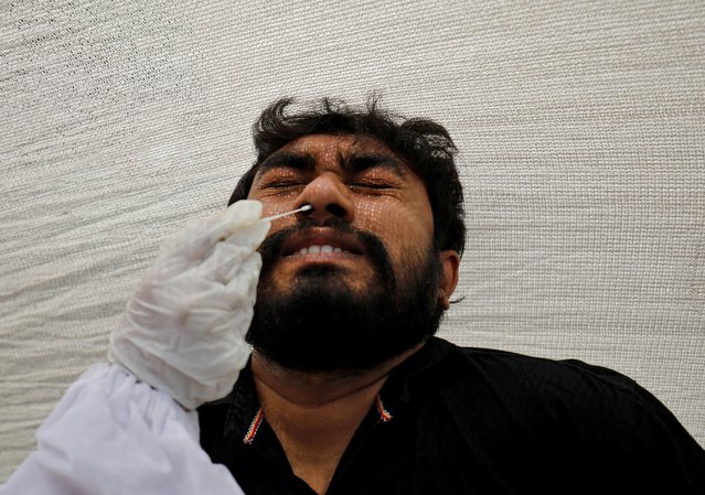 A man reacts as a healthcare worker collects a swab sample from him for a rapid antigen test during a testing campaign for coronavirus disease (COVID-19), at a kiosk in Ahmedabad, India, March 22, 2021. (Photo by Amit Dave/Reuters)