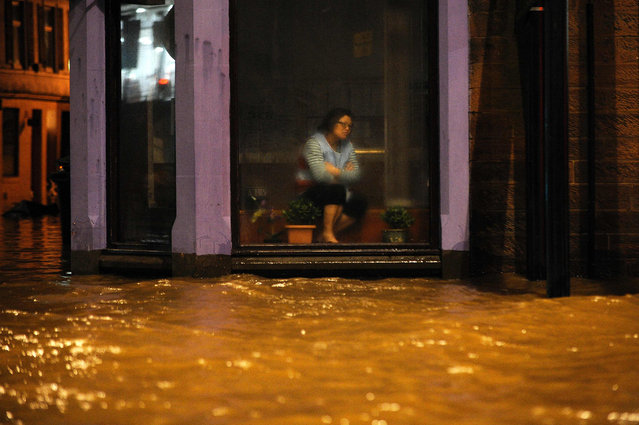 A woman sits inside a Chinese Restaurant watching floodwater race by the window in Dumfries, southern Scotland, on December 30, 2015 after heavy rainfall brought by Storm Frank. Storm Frank battered Scotland leaving thousands of homes without power and severe floods in its wake. (Photo by Andy Buchanan/AFP Photo)
