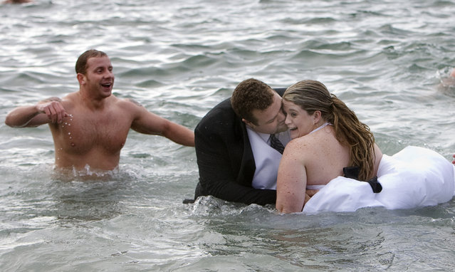 Gerhard Pyper (C) kisses his new bride Jan in the waters of English Bay after taking part in the 89th annual Polar Bear Swim in Vancouver, British Columbia January 1, 2009. The couple celebrated their wedding the night before with a cold swim in the bay. (Photo by Andy Clark/Reuters)