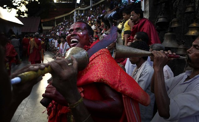 A Hindu priest, face smeared with color and sacrificial blood, gestures as he performs rituals during the two day long Deodhani festival at Kamakhya temple in Gauhati, India, on August 18, 2013. During this festival held to worship the serpent goddess, goats and pigeons are offered as sacrifice. (Photo by Anupam Nath/Associated Press)