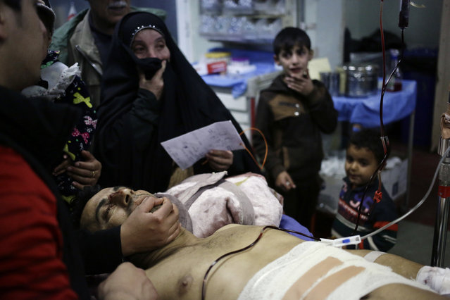 Relatives of an Iraqi injured soldier who was wounded in Mosul during the fighting between the Iraqi forces and the Islamic State militants, gather around him as he waits to receive medical treatment inside the emergency room of Rojava hospital, in Irbil, north Iraq, Sunday, November 27, 2016. The offensive to free Mosul of IS militants is now in its second month, and progress has slowed as troops try to avoid mass civilian casualties. (Photo by Hussein Malla/AP Photo)