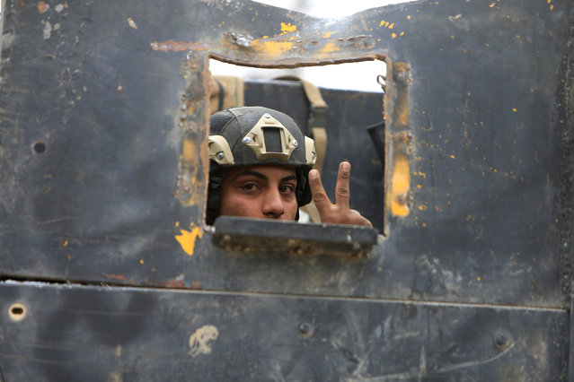 A member of the Iraqi Special Operations Forces (ISOF) gestures in military vehicle during a battle with Islamic State militants in Mosul, Iraq, November 30, 2016. (Photo by Alaa Al-Marjani/Reuters)