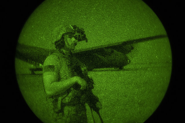 U.S. Army Spc. Dominic Deitrick, assigned to the 1-186th Infantry Battalion, Task Force Guardian, Combined Joint Task Force – Horn of Africa, seen through a night-vision device, provides security for a 75th Expeditionary Airlift Squadron (EAS) C-130J Super Hercules during unloading and loading operations Friday, June 12, 2020 at an unidentified location in Somalia. (Photo by Tech. Sgt. Christopher Ruano/Combined Joint Task Force – Horn of Africa via AP Photo)