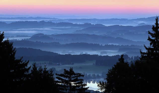 Early morning fog is visible in the valleys of the pre-alpine lands during sunrise near Bernbeuren, southern Germany, Friday, September 6, 2013. (Photo by Karl-Josef Hildenbrand/AP Photo/DPA)
