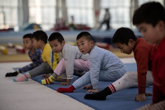 In this picture taken on January 12, 2021, young gymnasts train at the Li Xiaoshuang Gymnastics School in Xiantao, Hubei province. (Photo by Nicolas Asfouri/AFP Photo)