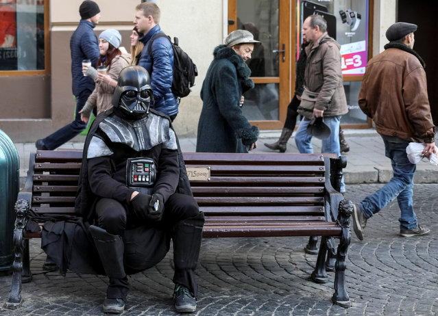 "A man dressed as the ""Star Wars"" character Darth Vader sits on a bench in central Lviv, Ukraine, November 24, 2016. (Photo by Gleb Garanich/Reuters)"