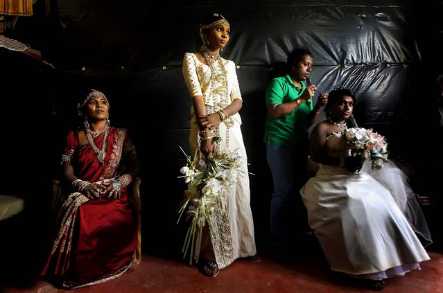 Former Tamil Tiger female rebel fighters and brides Nadarasa Sukirtha (L) and Premarathnam Sugandhini (C) look on as Jayarasa Merry Babila, an ethnic Tamil, get ready for a mass wedding in Kilinochchi,Sri Lanka, on September 18, 2013.Three ex-rebel couples who have been rehabilitated by the Sri Lankan Civil Defence Force were married as part of the government's rehabilitation program. (Photo by Dinuka Liyanawatte/Reuters)