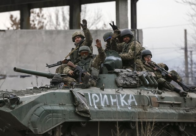 Ukrainian servicemen ride on a military vehicle near Artemivsk February 19, 2015. Fighting raged in eastern Ukraine on Thursday despite European efforts to resurrect a still-born ceasefire, a day after pro-Russian separatists who spurned the truce forced thousands of government troops out of a strategic town. (Photo by Gleb Garanich/Reuters)