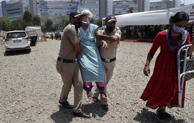 Police personnel help an elderly woman outside a vaccination centre In Mumbai, India, Saturday, April. 24, 2021. (Photo by Rajanish Kakade/AP Photo)