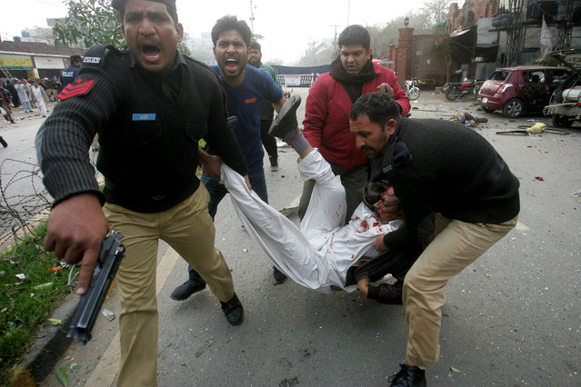 Pakistani police officers and volunteers rush an injured man to a hospital after a bombing in Lahore, Pakistan, Tuesday, February 17, 2015. (Photo by K. M. Chaudary/AP Photo)