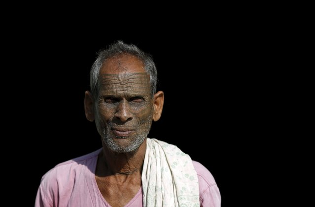 Bishram, 70, a follower of Ramnami Samaj, who has tattooed the name of the Hindu god Ram on his face, poses for a picture outside his house in the village of Arjuni, in the eastern state of Chhattisgarh, India, November 15, 2015. Denied entry to temples and forced to use separate wells, low-caste Hindus in the eastern state of Chhattisgarh first tattooed their bodies and faces more than 100 years ago as an act of defiance and devotion. (Photo by Adnan Abidi/Reuters)
