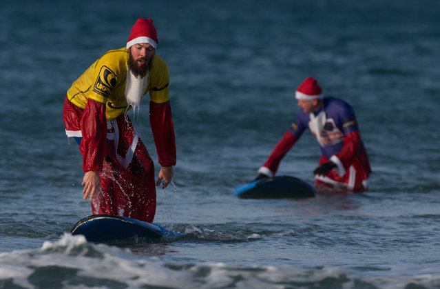 A surfer dressed as Santa gets to his feet as he braves the cold seas and near flat waves during the annual Surfing Santa as part of the Santa Run and Surf 2016 at Fistral Beach in Newquay on December 4, 2016 in Cornwall, England. (Photo by Matt Cardy/Getty Images)