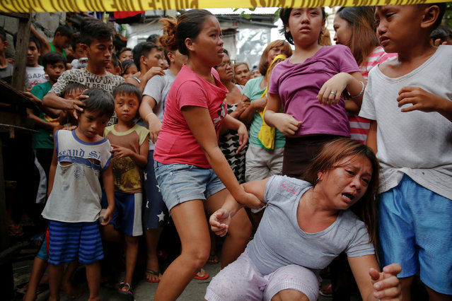 Janeth Mejos reacts as the body of her father Paquito Mejos is taken out of their home shortly after he was killed in a police operation in Manila, Philippines October 14, 2016. (Photo by Damir Sagolj/Reuters)