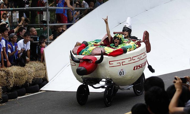"""Drivers of a traditional Taiwanese beef noodle soup """"soapbox"""" racer maneuver through the downhill course of the Red Bull Soapbox Race in Taipei, Taiwan, on September 29, 2013.  Racers judged on time and creativity competed for the top prize: a trip to the November 2013 Macau Grand Prix. (Photo by Wally Santana/Associated Press)"""