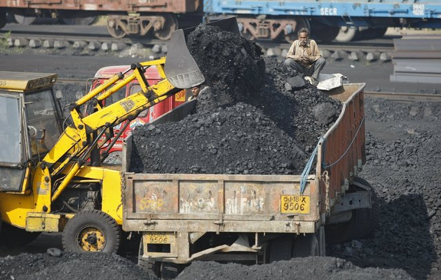 A worker sits on a truck being loaded with coal at a railway coal yard on the outskirts of Ahmedabad, India, in this November 25, 2013 file photo. (Photo by Amit Dave/Reuters)