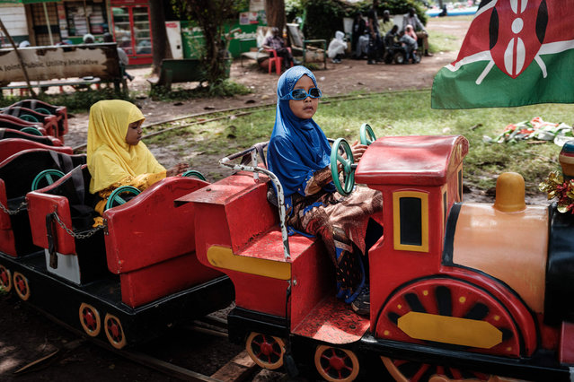 Muslim girls ride on a mini train after attending the Eid Al-Fitr prayer that marks the end of the Holy month of Ramadan at Uhuru Park in Nairobi, Kenya, on May 13, 2021. (Photo by Yasuyoshi Chiba/AFP Photo)