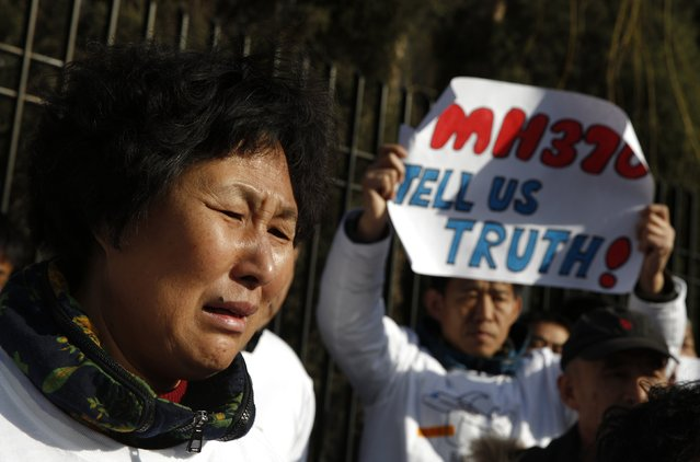 Liu Guiqiu, whose son was onboard the missing Malaysia Airlines flight MH370, cries during a gathering of family members of the missing passengers outside the Malaysian embassy in Beijing March 8, 2015. Malaysian and Chinese officials say they are committed to the search for MH370 and in assisting families who are still waiting for concrete information on what happened to their loved ones a year ago.