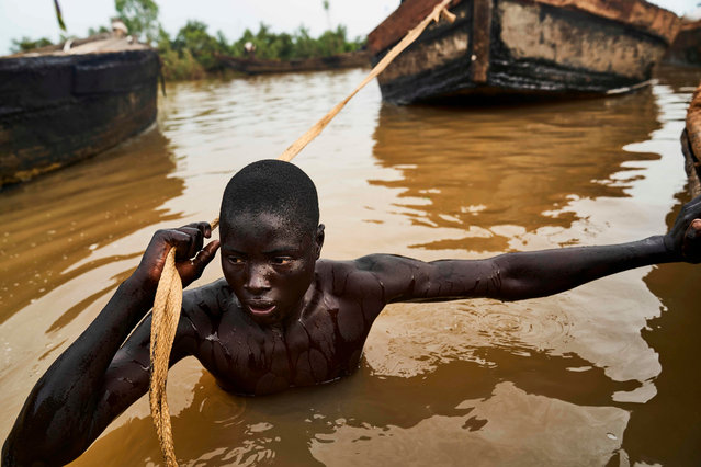 A Malian digger pulls his boat to a site where he can dive and collect sand from the Niger river bed near Kangaba, in Mali' s southwestern Koulikoro region, on October 2, 2018. (Photo by Michele Cattani/AFP Photo)
