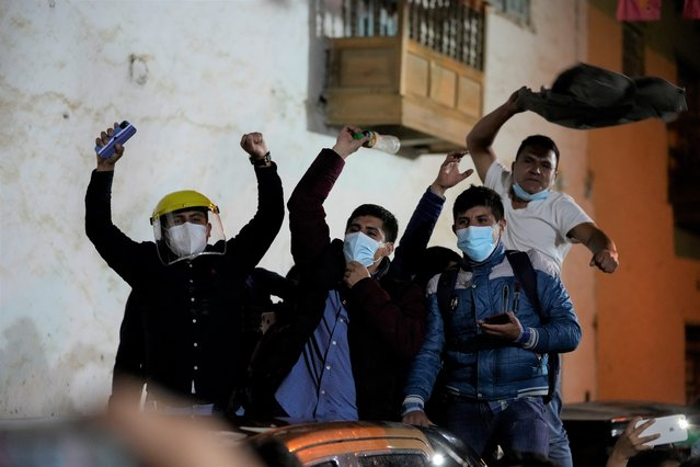 Supporters of presidential candidate Pedro Castillo cheer in the street during a runoff election, in Tacabamba, Peru, Sunday, June 6, 2021. Peruvians voted in a presidential run-off election to choose between Fujimori, the daughter of jailed ex-President Alberto Fujimori, and Pedro Castillo, a political novice that until recent was a rural schoolteacher. (Photo by Martin Mejia/AP Photo)