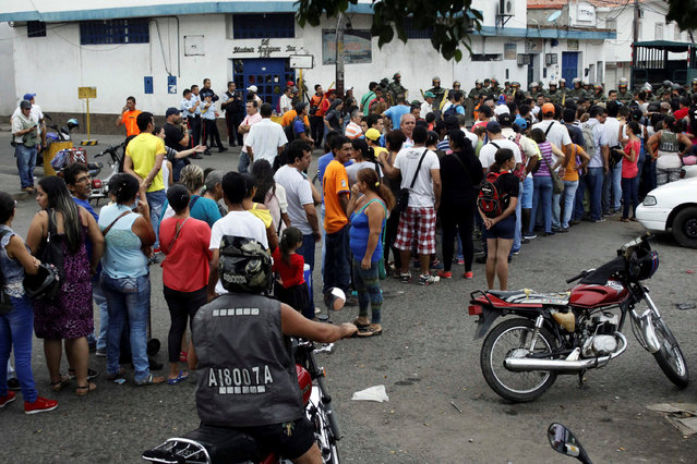 People make a line in front of Venezuelan National Guards as they wait to try to cross the border to Colombia over the Francisco de Paula Santander international bridge in Urena, Venezuela December 18, 2016. (Photo by Carlos Eduardo Ramirez/Reuters)