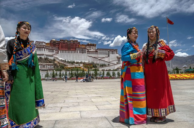 Women wear traditional style clothing as they pose for photos in the square in front of the Potala Palace, a UNESCO heritage site, during a government organized visit for journalists on June 1, 2021 in Lhasa, Tibet Autonomous Region, China. (Photo by Kevin Frayer/Getty Images)