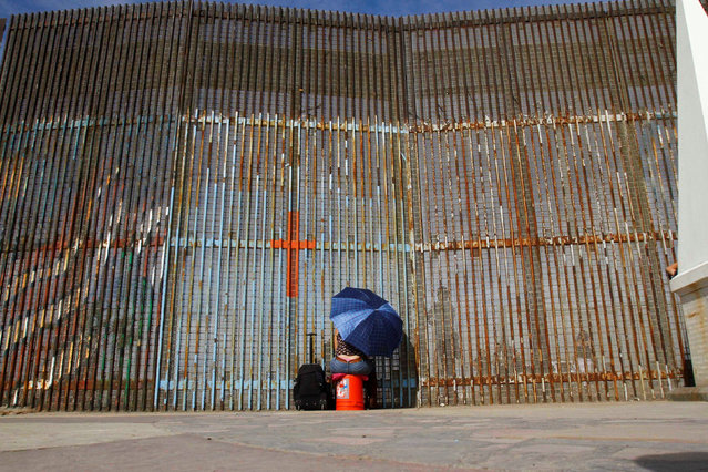 MEXICO: A woman talks to her relatives across a fence separating Mexico and the United States, in Tijuana, Mexico, November 12, 2016. (Photo by Jorge Duenes/Reuters)