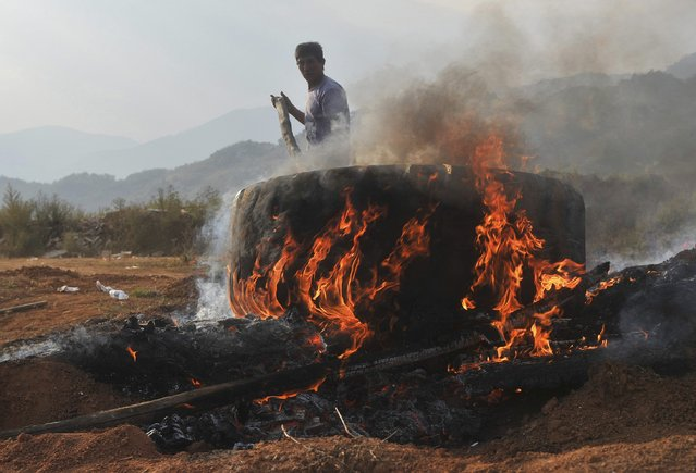 A man cremates the bodies of his relatives, who according to him were killed in clashes between the Myanmar Army and the Myanmar National Democratic Alliance Army (MNDAA) at Myanmar's border town with China, in Kokang February 16, 2015. (Photo by Reuters/Stringer)