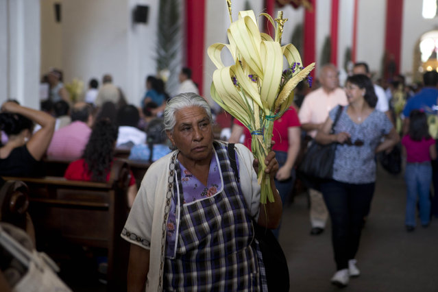 A Mayan woman holds bouquets of palm fronds as she leaves the San Francisco Catholic Church after attending the traditional Palm Sunday Mass, marking the start of Holy Week ahead of Easter, in Antigua, Guatemala, Sunday, March 29, 2015. (Photo by Moises Castillo/AP Photo)