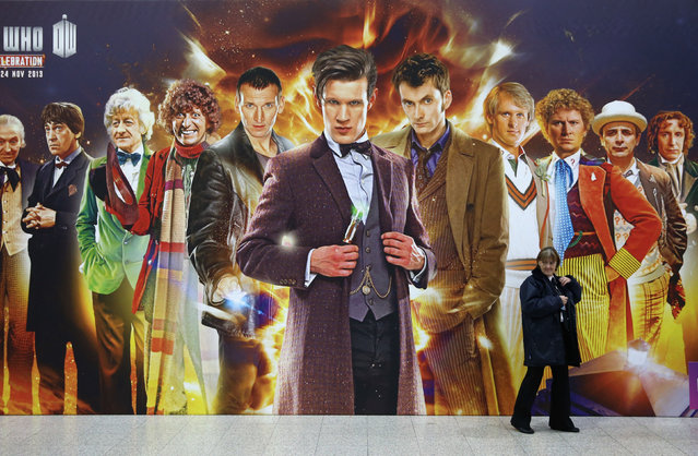 "A security guard walks past a giant Doctor Who poster at the ""Doctor Who 50th Celebration"" event in the ExCeL centre on November 22, 2013 in London, England. The sold-out three day event in the ExCeL London convention centre celebrates 50 years of the show which has seen 11 actors play the role of Doctor Who and receives a worldwide cult following. (Photo by Oli Scarff/Getty Images)"