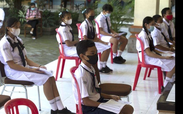 Teenagers wait to receive a shot of the Sinovac vaccine for COVID-19 during a vaccination campaign at a school in Denpasar, Bali, Indonesia on Monday, July 5, 2021. (Photo by Firdia Lisnawati/AP Photo)
