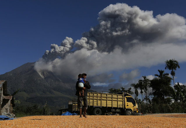 A man holds his son while walking on dried corn with Mount Sinabung spewing ash in the background at Sibintun village in Karo district, November 25, 2013. (Photo by Reuters/Beawiharta)