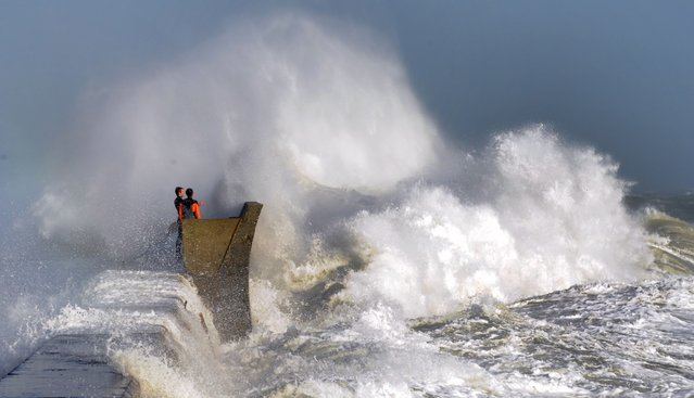 People play in front of waves on the jetty of the harbour of Lesconil, western of France on February 8, 2016. (Photo by Fred Tanneau/AFP Photo)