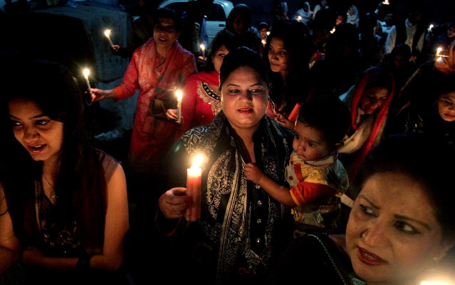 Christians light candles during Easter service in Karachi, Pakistan, Sunday, April 5, 2015. (Photo by Fareed Khan/AP Photo)