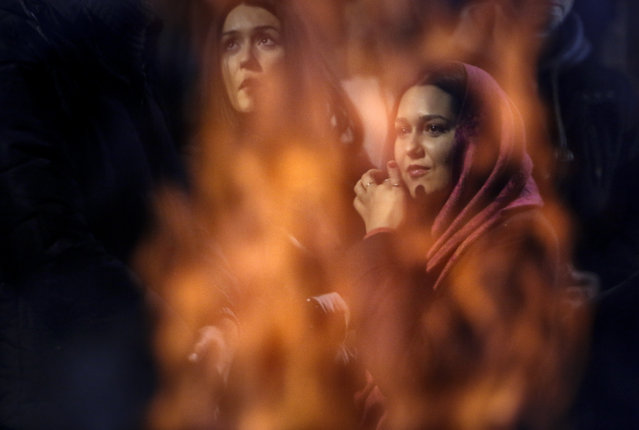 In this Saturday, January 6, 2018, picture, Bosnian Serb women, seen through flames, attend a ceremonial burning of dried oak branches during the Orthodox Christmas eve religious service at the Orthodox church in the Bosnian capital, in Sarajevo, Bosnia. Like many other Orthodox Christians around the world, Serbs observe holidays according to the Julian calendar instead of the Gregorian calendar adopted during the 16th century. That means they celebrate Christmas on Jan. 7 instead of Dec. 25. (Photo by Amel Emric/AP Photo)