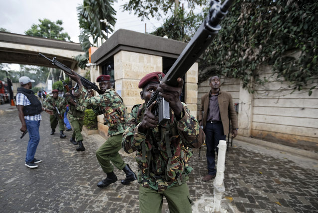 Kenyan security forces aim their weapons up at buildings as they run through a hotel complex in Nairobi, Kenya Tuesday, January 15, 2019. Terrorists attacked an upscale hotel complex in Kenya's capital Tuesday, sending people fleeing in panic as explosions and heavy gunfire reverberated through the neighborhood. (Photo by Ben Curtis/AP Photo)