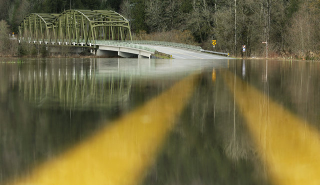 Water from the nearby Snoqualmie River sits over NE Tolt Hill Road, Tuesday, February 16, 2016, near Carnation, Wash. The road and others were closed Tuesday after a President's Day storm brought record rainfall to the Pacific Northwest. (Photo by Ted S. Warren/AP Photo)