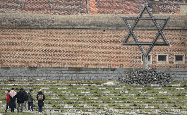 Visitors walk through the cemetery of the former Nazi concentration camp in Terezin, Czech Republic, Thursday, January 24, 2019. A unique collection of some 4,500 drawings by children who were interned at the Theresienstadt concentration camp during the Holocaust now displayed in the Pinkas Synagogue, still attracts attention even after 75 years since their creation. The drawings depict the everyday life as well hopes and dreams of returning home. (Photo by Petr David Josek/AP Photo)