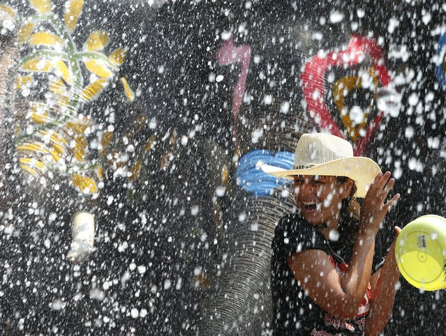 A foreigner reacts as she gets sprayed with water from elephants to preview the upcoming Songkran Festival celebration, the Thai traditional New Year, also known as the water festival at the ancient world heritage city of Ayutthaya, Thailand, 10 April 2015. (Photo by Narong Sangnak/EPA)