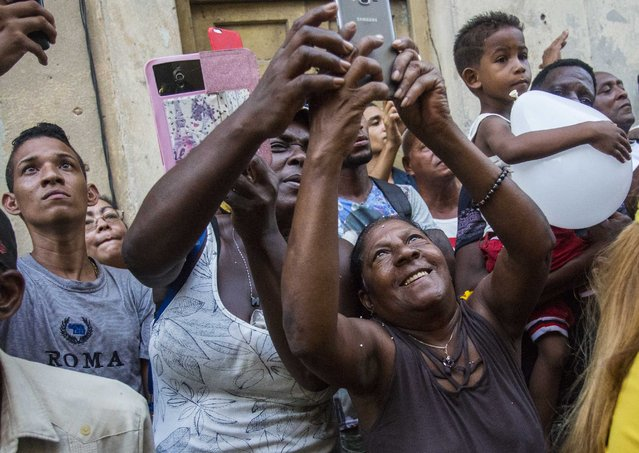 """In this Sept. 8, 2018 file photo, people take pictures of the statue of the Virgin of Charity during an annual religious procession in Havana, Cuba. Cuba's patron saint is also recognized as a powerful deity in the African-influenced religion of Santeria, which refers to her as """"Ochun"""". (Photo by Desmond Boylan/AP Photo)"""