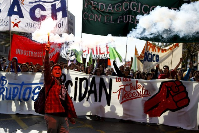 A student holds up a flare as others shout slogans during a demonstration against the government to demand changes in the education system at Santiago, April 16, 2015. (Photo by Ivan Alvarado/Reuters)